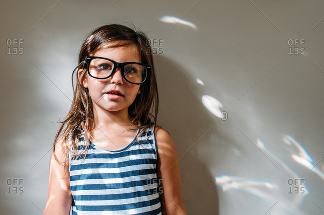 Portrait of a young girl wearing an adult's eyeglasses