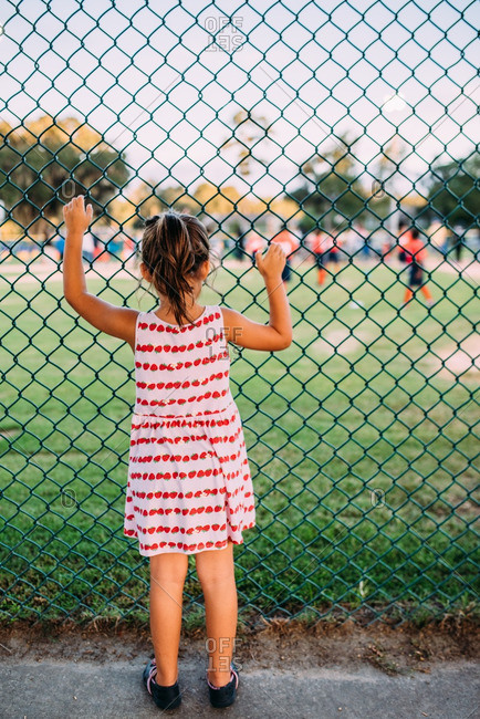Girl holding fence and watching football game