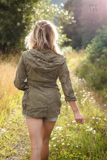 Back view of woman walking through field