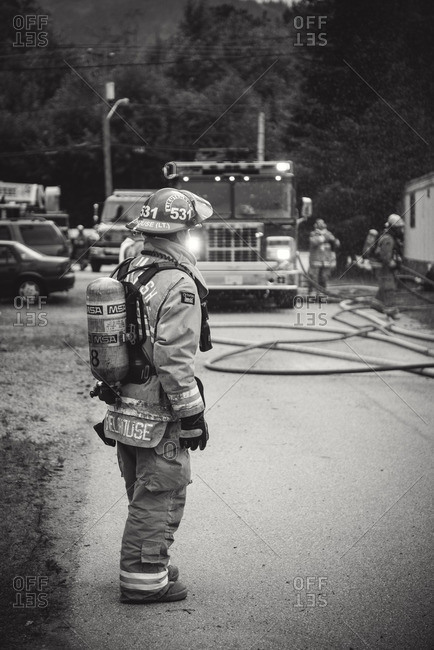 Squamish, British Columbia - August 9, 2016: Fire Lieutenant in full firefighting gear standing on street at site of blaze