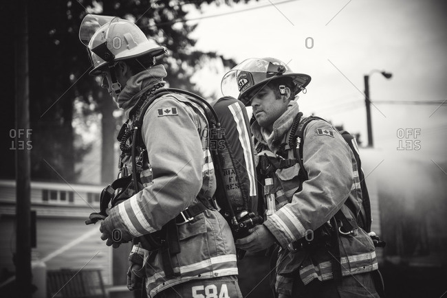 Squamish, British Columbia - August 9, 2016: Two firemen in full firefighting gear on scene at trailer fire