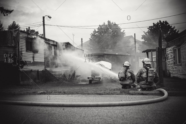 Squamish, British Columbia - August 9, 2016: Firemen spraying a smoldering fire in a house trailer