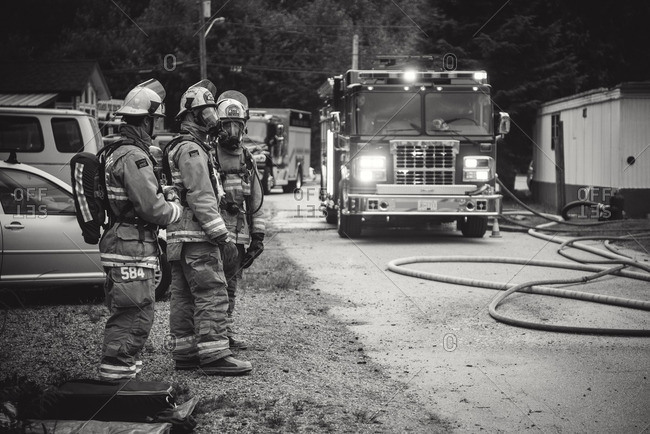 Squamish, British Columbia - August 9, 2016: Three firemen and a fire truck at a trailer park fire