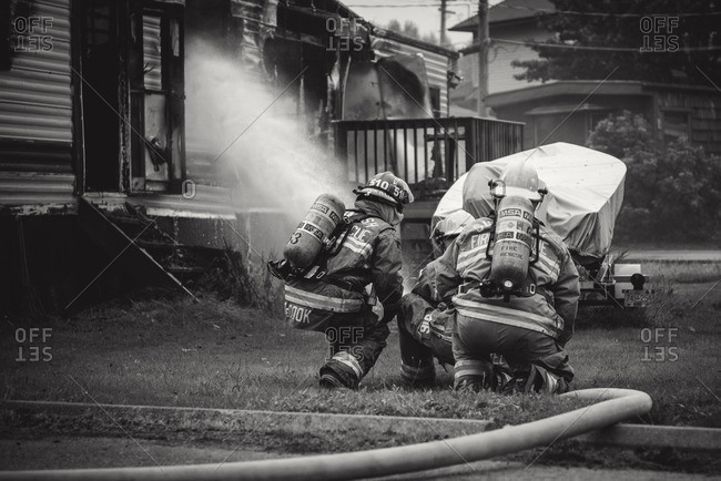 Squamish, British Columbia - August 9, 2016: Firemen working together to extinguish a trailer fire