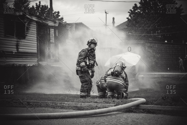 Squamish, British Columbia - August 9, 2016: Firefighters in respirators working to extinguish trailer fire