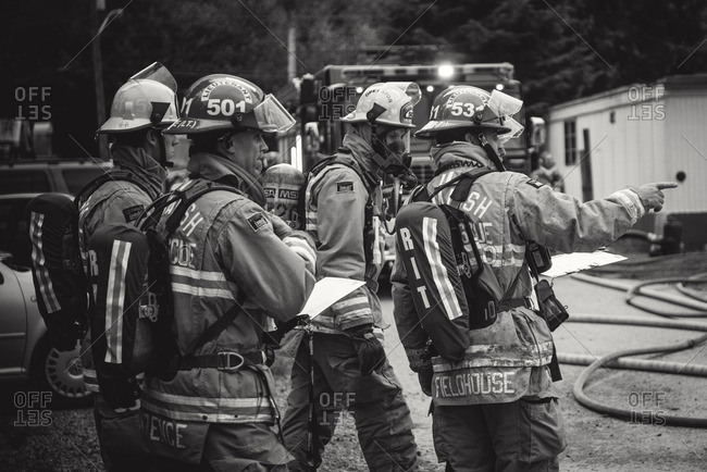 Squamish, British Columbia - August 9, 2016: Four firemen in gear surveying scene of fire
