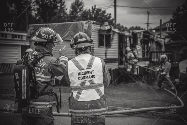 Squamish, British Columbia - August 9, 2016: Lieutenant and Incident Commander work together at scene of trailer fire