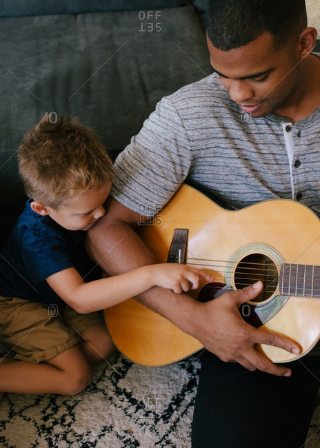 Father showing his son how to play guitar