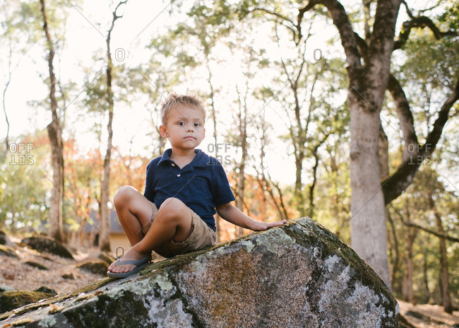 Little boy sitting on a large mossy rock