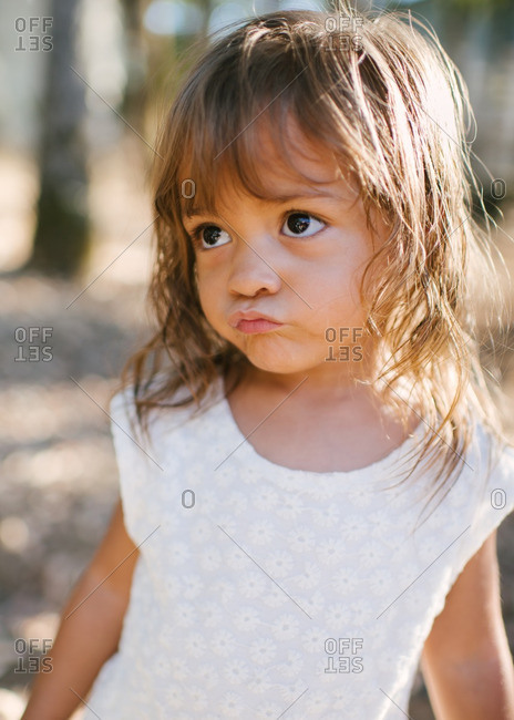 Portrait of a little girl pursing her lips outdoors