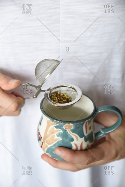 Person preparing to steep tea infuser into a cup of water