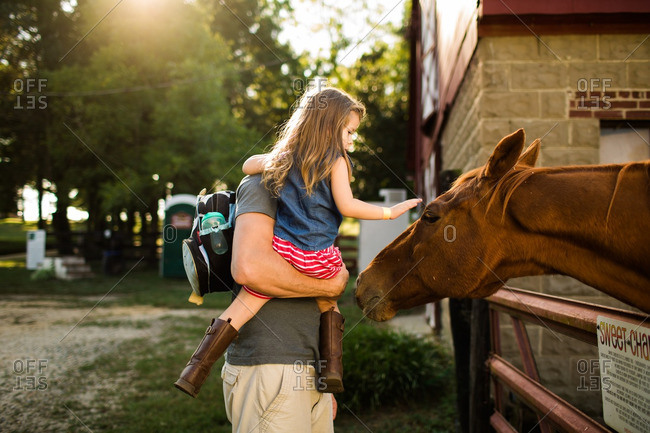 Father holding his daughter as she pets a horse in a barnyard