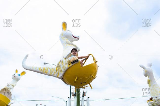 Boy riding a kangaroo-shaped carnival ride