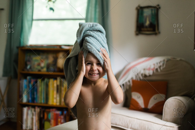 Boy with a towel wrapped around his head making a silly face