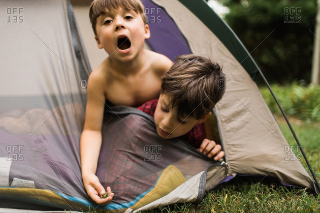 Two boys hanging from the door of a tent making silly faces