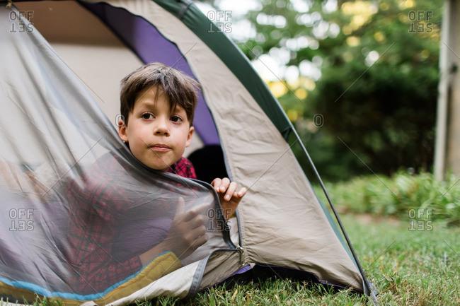 Boy poking his head from an open tent door