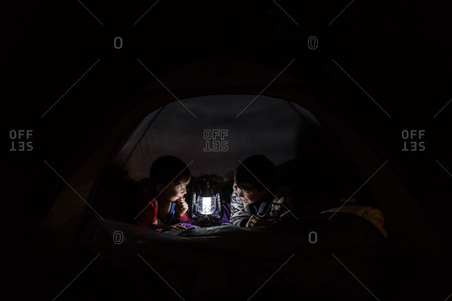 Brothers lying in a tent looking at a lamp at night