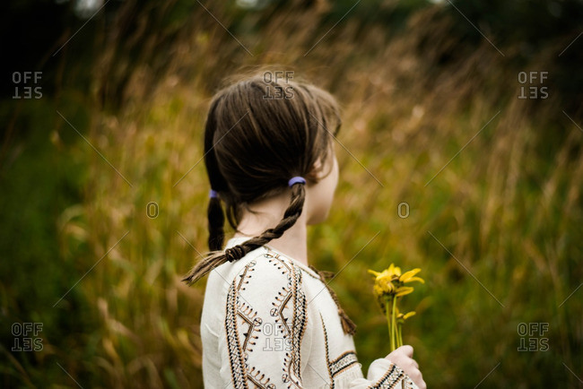 Girl with braided hair holding wildflowers in a meadow