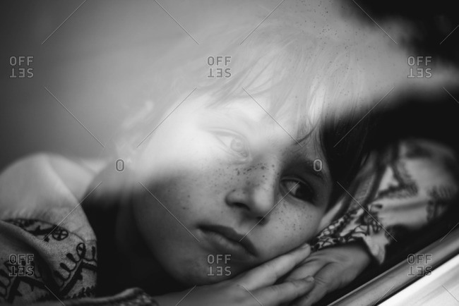 Portrait of a girl resting her head on her arm while looking out the car window