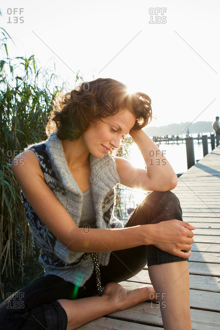 Smiling woman sitting on pier