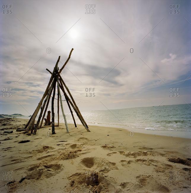 Log teepee on sandy beach