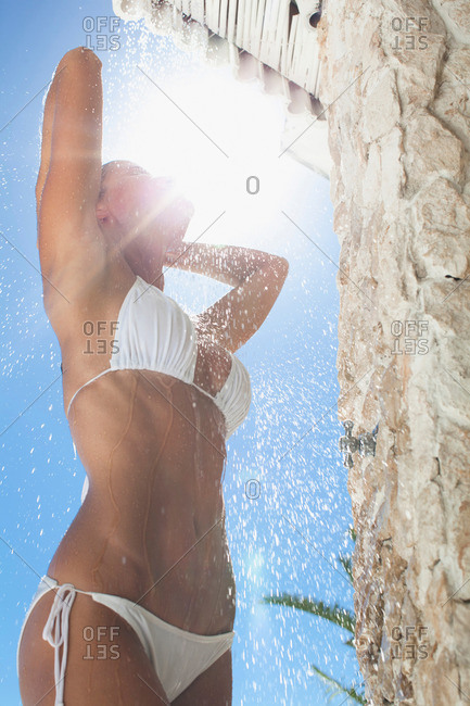 Woman rinsing off in outdoor shower
