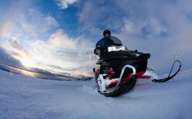 Man driving snowmobile in snowy field