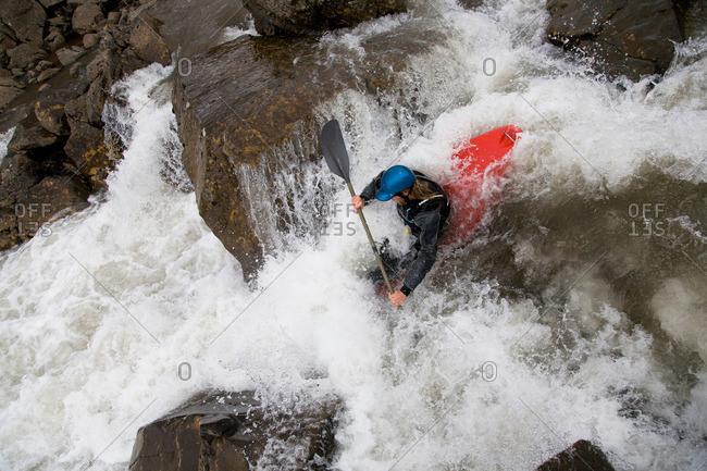 Man canoeing over rocky waterfall