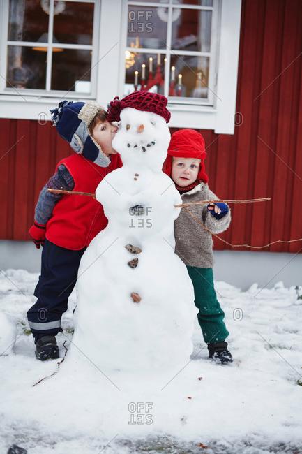 Children standing with snowman