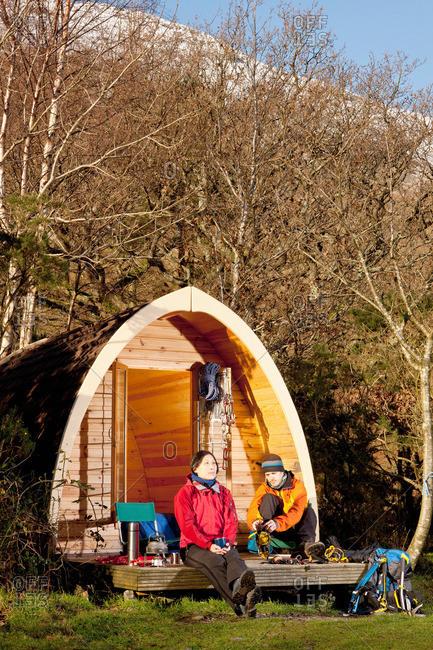 Climbers sitting outside camping pod