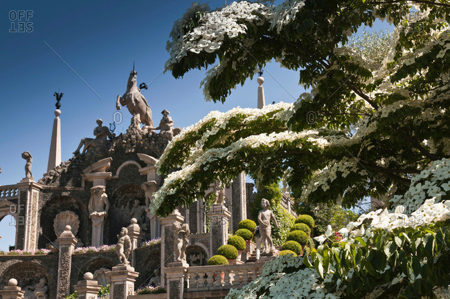 Tree by ornate statues and columns