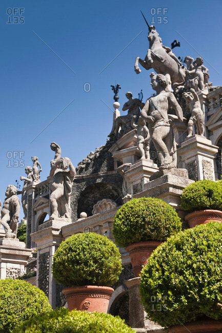 Shrubs with ornate statues and columns