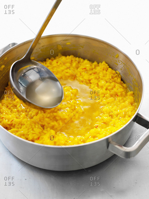Soup ladled into pot of risotto