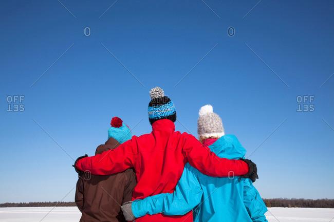 Friends hugging in snowy field
