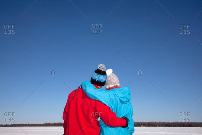 Couple hugging in snowy field