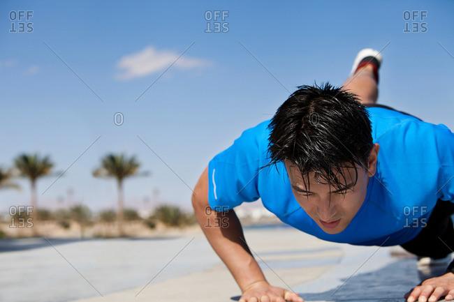 Athlete doing push-ups outdoors