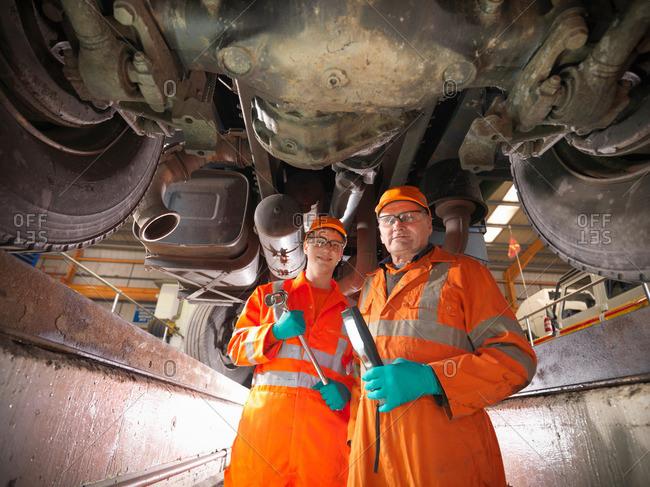 Apprentice engineer and engineer inspecting underneath truck