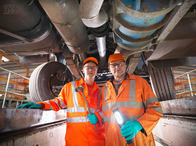 Apprentice engineer and engineer underneath truck