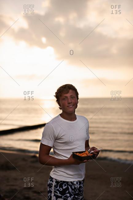 Teenage boy eating on beach