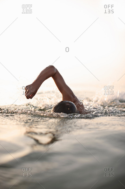 Teenage boy swimming in water