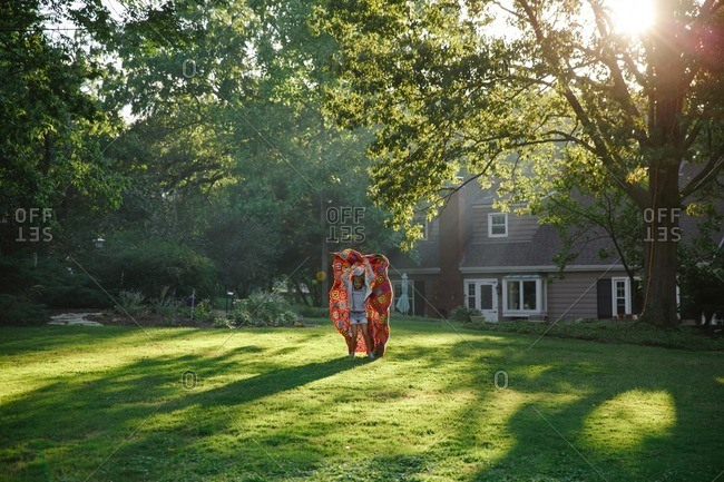 Girl playing with blanket in yard