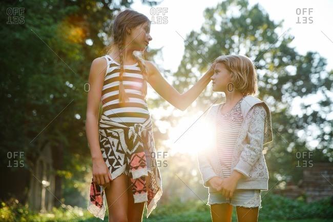 Loving girls in sun dappled yard
