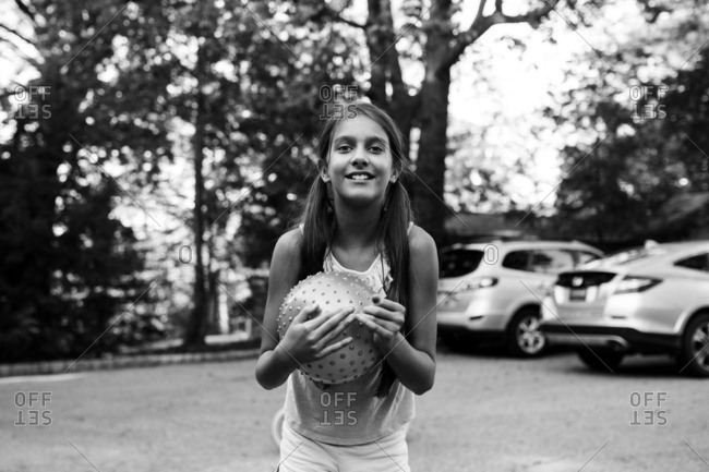 Girl holding ball on a driveway