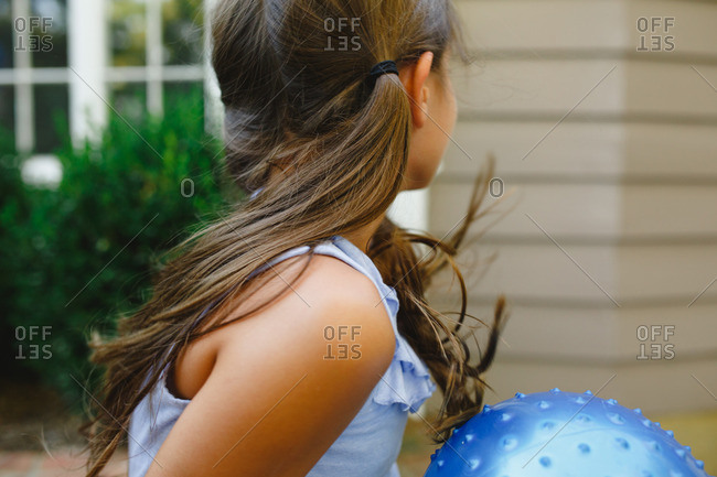 Girl with brown pigtails holding ball