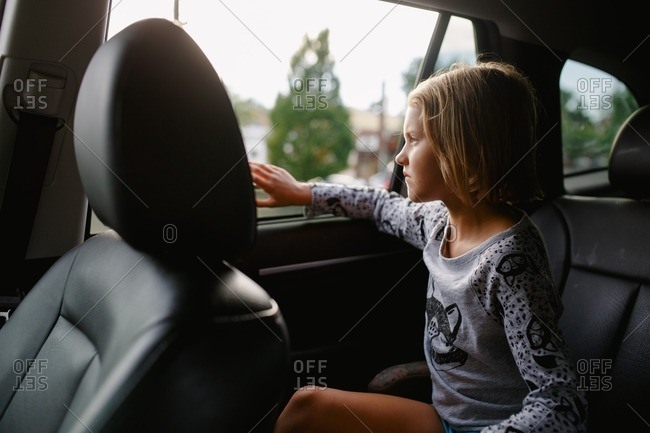 Girl staring off in backseat of a car