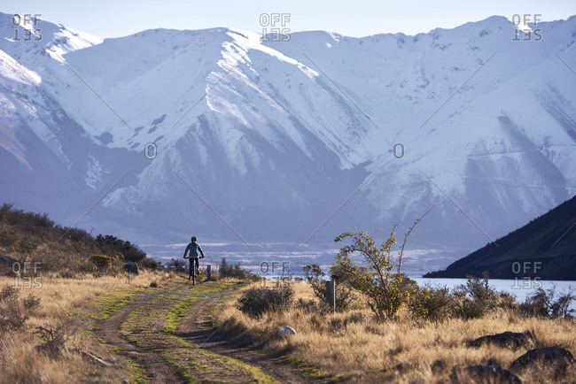 Mountain biking down Alps to ocean track with a lake and snow covered mountains in the background
