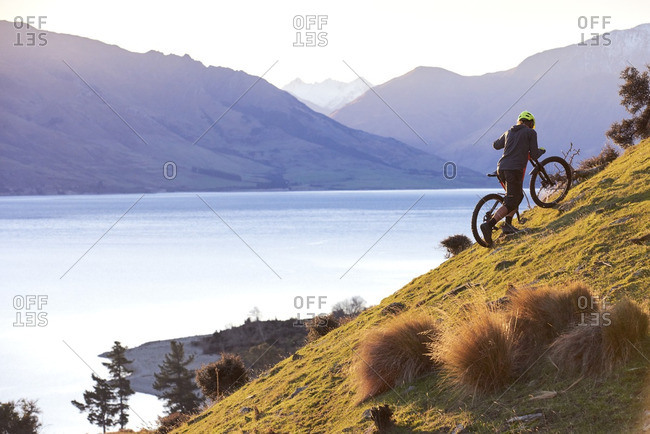 Man pushing a mountain bike up at a hill at sunset with a lake and mountains in the background