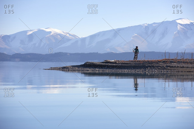 Girl mountain biking along a lake with a reflection and snowy mountains in the background