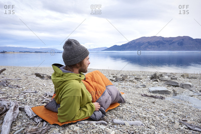 Man lying in a sleep bag on a mat by the side of a lake with mountains in the background