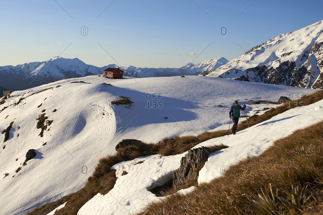Girl walking in snow in the mountains with a hut in the background